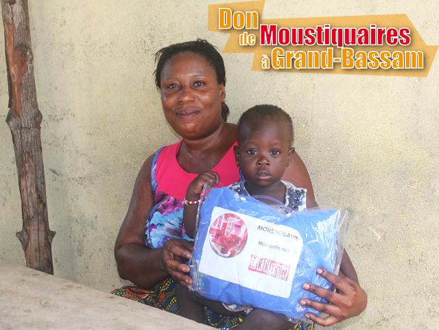 Avec sa fille sur le pied, une nourrice pose avec sa moustiquaire imprégnée après une séance de sensibilisation autour du paludisme à Grand-Bassam Embouchure, Côte d'Ivoire.